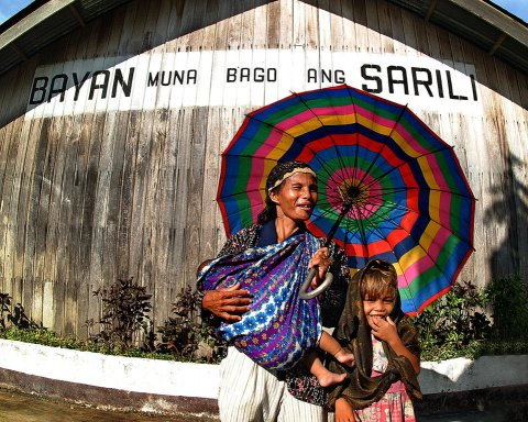 """In the Philippines, a mother with two children stands in front of a school building with a slogan for Muslim war refugees: """"Country first before self."""" © 2003 Samuel De Leon, Courtesy of Photoshare"""