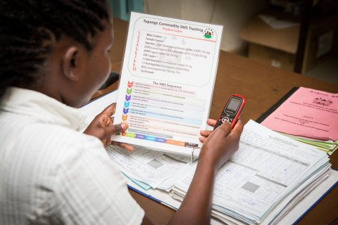 In Nairobi, Kenya, a facility in-charge uses her phone and a system job aid to submit a monthly CDRR (consumption data report and request form) to the Tupange SMS commodity tracking system (TSCTS). © 2014 John Kihoro/Tupange(Jhpiego Kenya), Courtesy of Photoshare
