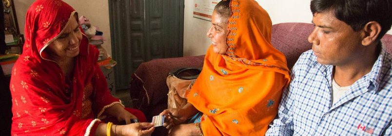 Mrs. and Mr. Yaqub receive oral contraceptives from health worker Shahnaz Kousar at her home office in Punjab Province, Pakistan. © 2012 Derek Brown/USAID, Courtesy of Photoshare