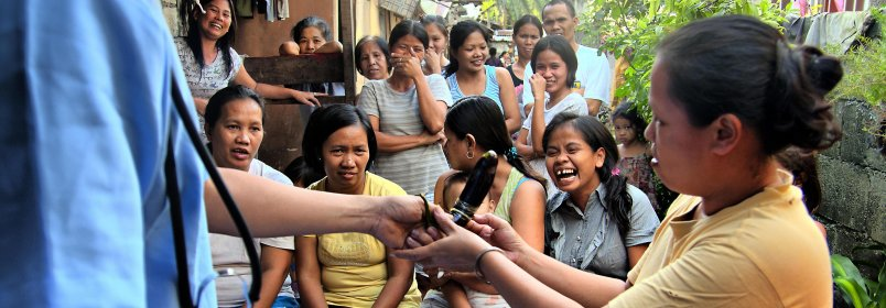 Government and volunteer health workers demonstrate condom use during an information drive in Antipolo, Philippines, to raise health awareness in the fight against HIV/AIDS and the importance of family planning. © 2012 RJCabagnot, Courtesy of Photoshare