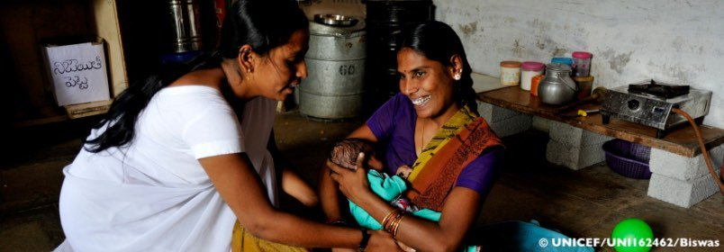 Smiling mother with her baby being helped by another woman
